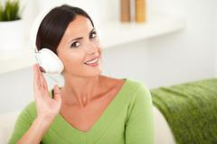 Smiling caucasian woman in green shirt listening to music with focus on fore - stock photo