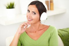 Horizontal portrait of a beautiful carefree woman listening to music on headp - stock photo