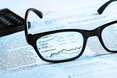 Financial chart and graph currencies see through glasses lens on financial ne Stock Photos