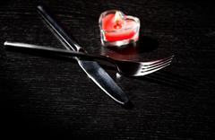 Valentine day table setting with knife, fork, red burning heart shaped candle Stock Photos