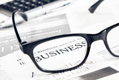 business word see through glasses lens on financial newspaper near calculator - stock photo