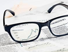 financial chart and graph of stock indexes see through glasses lens on financ - stock photo