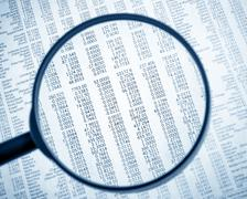 financial data see through lens of loupe on financial newspaper - stock photo