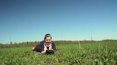 Girl lying on the grass with the tablet. Camera movement with the slider Stock Footage