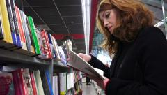 Cultured young woman reading some books in a bookstore Stock Footage