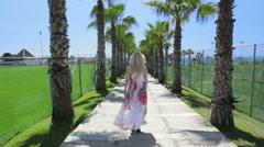Blond lady walking along palm tree walkway. Stock Footage