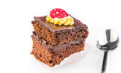 Delicious slice of chocolate cake with cream and sugar candy on top near a sp Stock Photos