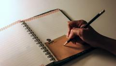 Zoom in writing heart on a note pad Stock Footage