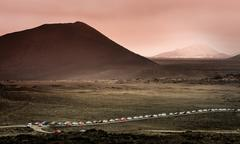 mountain landscape with a queue of cars - stock photo