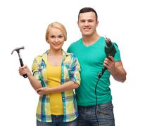 Smiling couple with hammer and drill Kuvituskuvat
