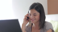 Nice girl browsing internet talking over the phone at home close up Stock Footage