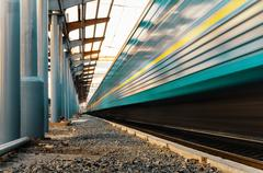 High speed passenger train on tracks with motion blur effect - stock photo