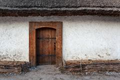Wooden old door with lock and clay wall. Background Stock Photos