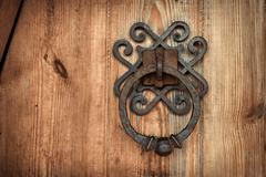 old rusty doorknob and wood door - stock photo