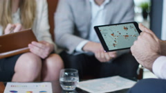 4K Business team in a meeting, looking at world map on computer tablet - stock footage