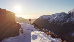 Man glassing on mountain side before sunset. - stock footage