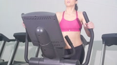 Woman working out on cross trainer slow motion a Stock Footage