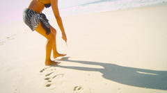 Beautiful woman writing in the sand on a beach Stock Footage
