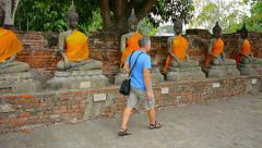 Tourist Visits Ancient Buddha Statues at Wat Yai Chai Mongkol in Thailand Stock Footage