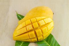 Stock Photo of Close up yellow mango on wood background