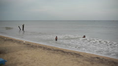 Indian children playing the ocean, long shot Stock Footage