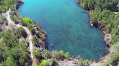 Flooded quarry in the forest. Aerial view. The camera moves back Stock Footage