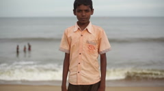 A young Indian boy staring at the camera asking for a photo, Medium shot Stock Footage