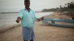 Fisherman in India organizing his fishing net, medium long shot, shallow focus Stock Footage