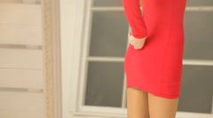 Young beautiful girl in front of a mirror in a red dress in stockings.  Stock Footage