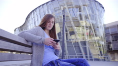 Longhair girl with phone in front of curved business buildings Stock Footage