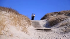 Dunes. At the top of the dunes couple in love, on a slope dune passes staircase Stock Footage