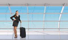 Flight attendant standing with luggage in airport - stock photo