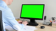 man works on desktop computer in the office - green screen - stock footage