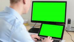 Man works on desktop computer and laptop in the office - green screen Stock Footage
