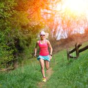 Girl athlete runs into the forest and meadow Stock Photos