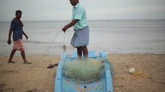 Fisherman in India organizing fishing net, long shot, front, ocean background Stock Footage