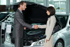 Car salesperson shaking hands with customer at showroom Stock Photos