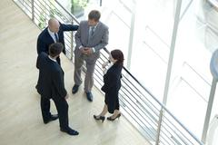 Businessmen and woman standing together by railing conversing Stock Photos