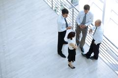 Businessmen and woman standing together by railing and conversing Stock Photos