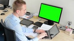 Young handsome man works on laptop computer in the office - green screen Stock Footage