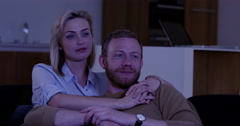 Attractive couple watching scary TV in dark room in contemporary home, slow - stock footage