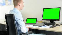 Man sits and looks on desktop and laptop computer in office - green screen Stock Footage