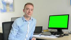 Young handsome man sits and works and then smiles - computer green screen Stock Footage