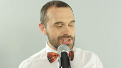 Close-up of a blue-eyed singer performs a song in a microphone on a white Stock Footage