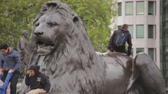 Tourists Climbing on Lion Sculpture Stock Footage