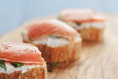 Small sandwiches with soft cheese and salmon on wood table Stock Photos