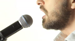 Close-up of a blue-eyed man with a beard wearing a jacket singing a song into Stock Footage