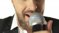 Close-up of a young handsome man energetically singing the song into the Stock Footage