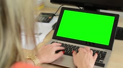 Young attractive woman working on the laptop computer in office - green screen Stock Footage