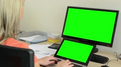 Young attractive woman working on the laptop and desktop computer-green screen Stock Footage
